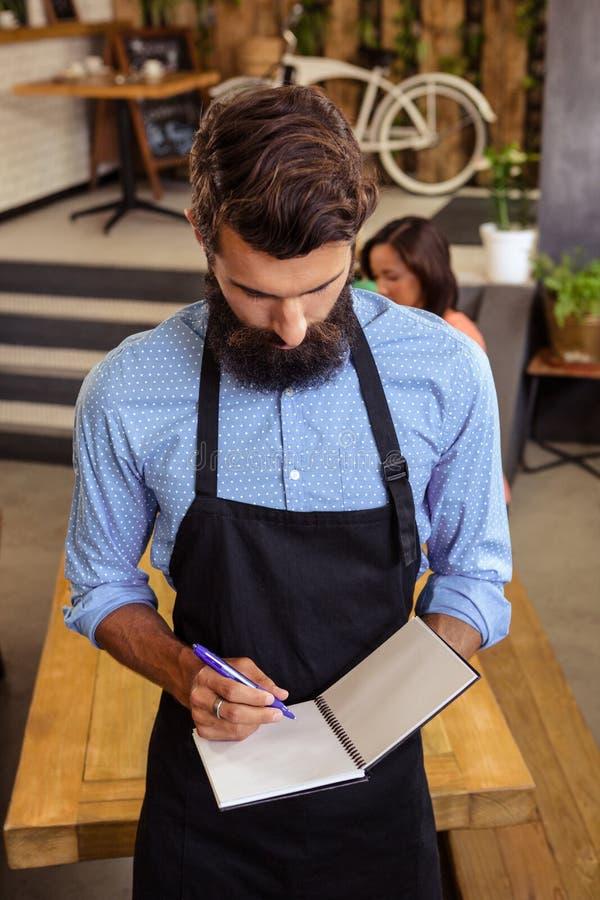 Kelner bierze rozkaz w jego książce fotografia royalty free