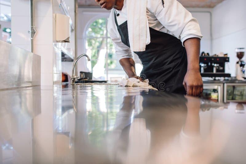 Kelner die de tegenbovenkant in de keuken afvegen stock fotografie