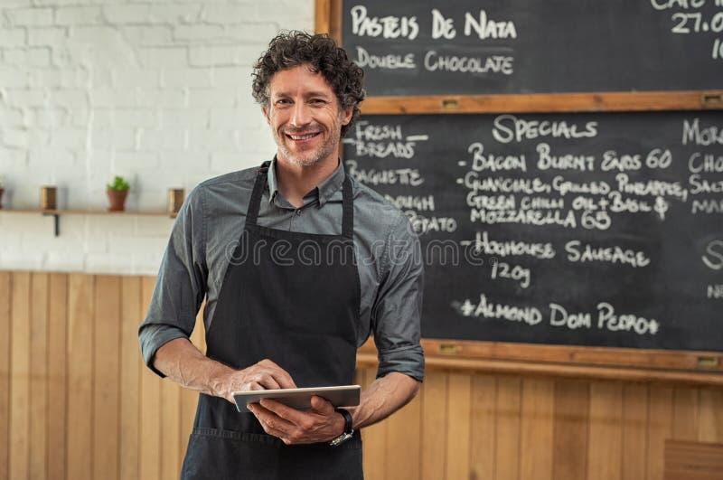 Kelner die digitale tablet houden bij cafetaria royalty-vrije stock afbeeldingen
