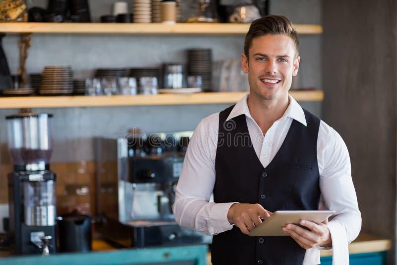 Kelner die digitale tablet in restaurant houden stock afbeelding