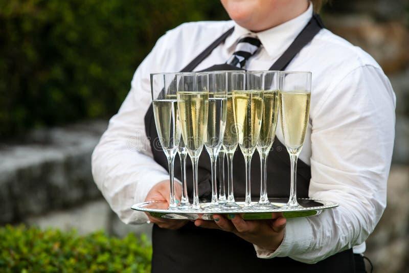 Kelner die een dienbladhoogtepunt van dranken houden tijdens een gericht huwelijk of andere speciale gebeurtenis stock fotografie