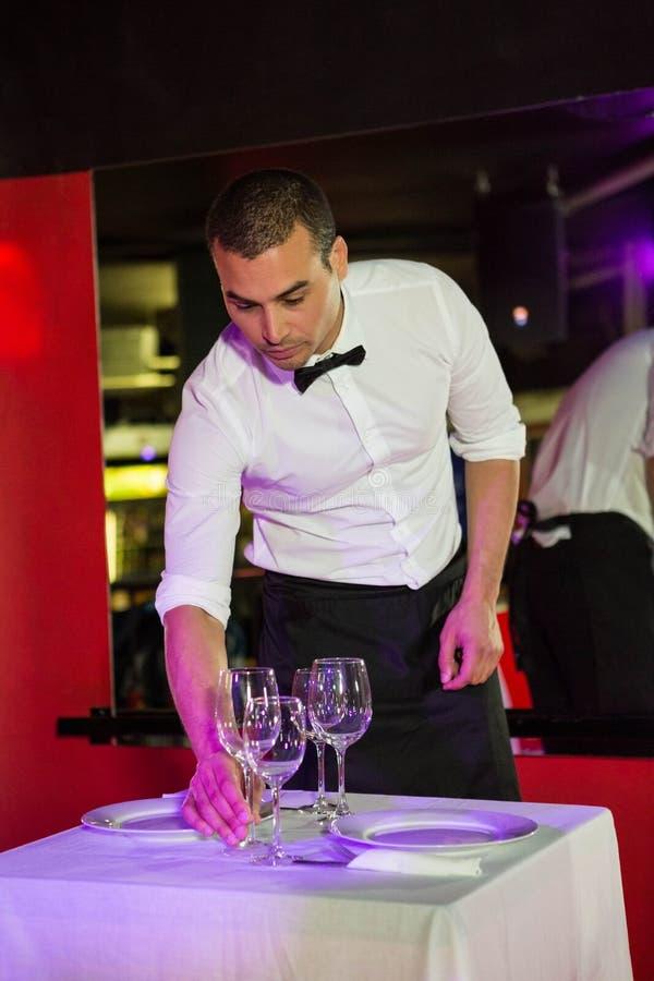 Kelner die een lijst plaatsen stock afbeeldingen