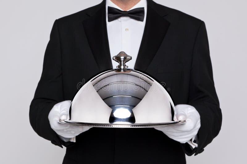Kelner die een zilveren glazen kap houden stock foto
