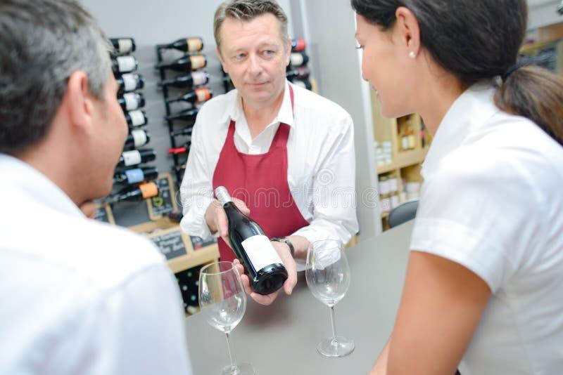Kelner die flessen rode wijn voorstellen stock fotografie