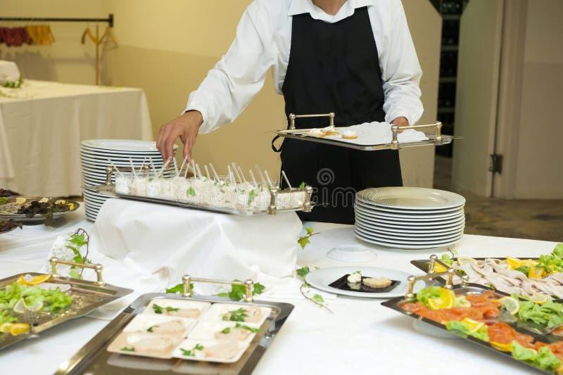 Kelner die huwelijksbuffet voorbereiden stock afbeeldingen