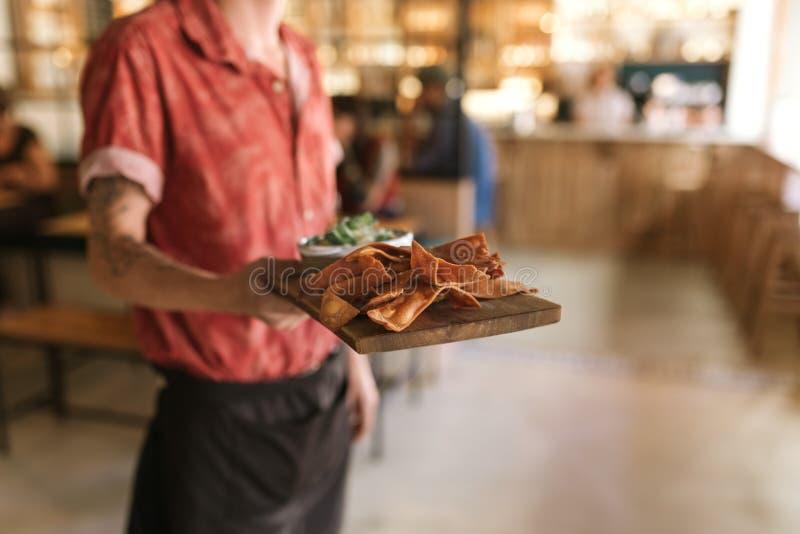 Kelner die omhoog een raad van vers gebakken nachos dienen stock foto's