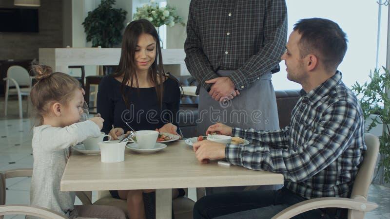 Kelner die orde samen nemen bij lijst van familie die diner hebben Zij die gelukkig en tevreden kijken stock afbeeldingen