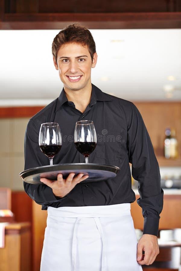 Kelner die rode wijn in restaurant dienen stock afbeeldingen