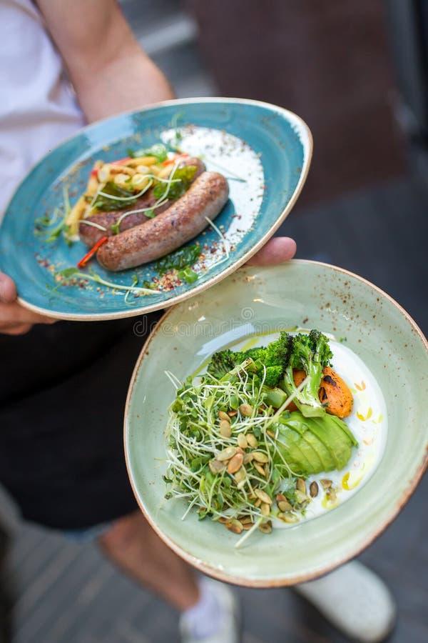 Kelner die twee platen met heerlijke ontbijtchef-kok houden die voedsel in restaurant voorstellen Twee platen met salade, worsten stock foto