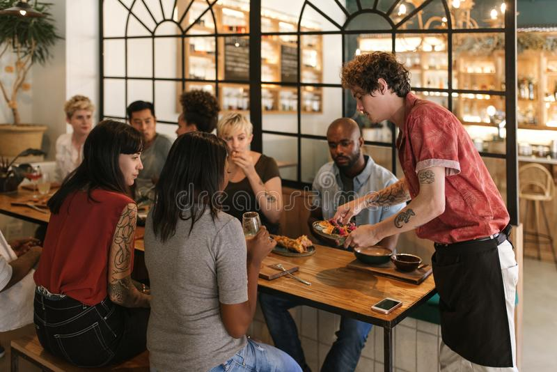 Kelner die vers gemaakt voedsel dienen aan glimlachende bistroklanten stock afbeeldingen