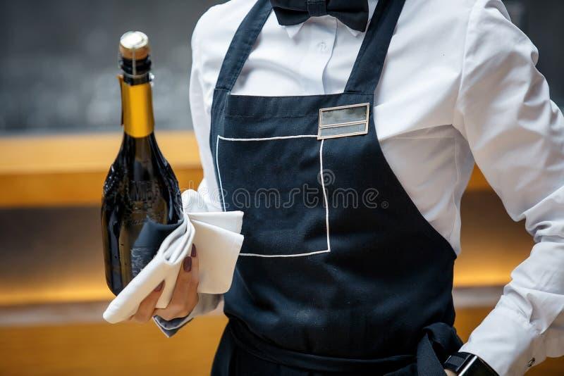 Kelner in een restaurant met een fles van prosecco stock foto
