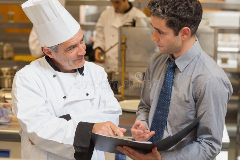 Kelner en chef-kok die het menu bespreken stock foto
