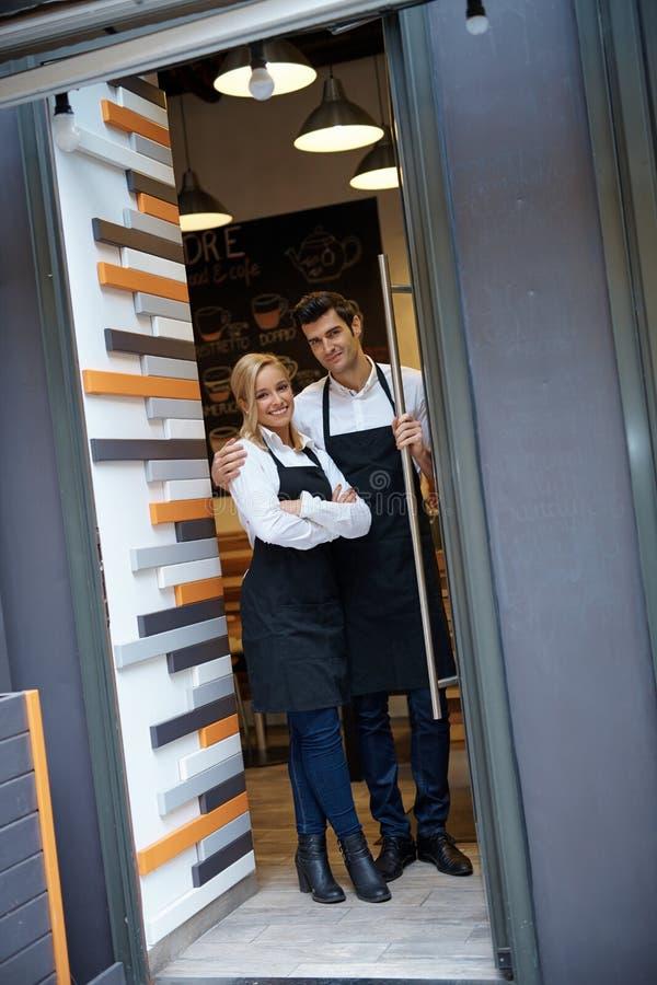Kelner en serveerster die zich bij ingang van koffie bevinden royalty-vrije stock afbeelding