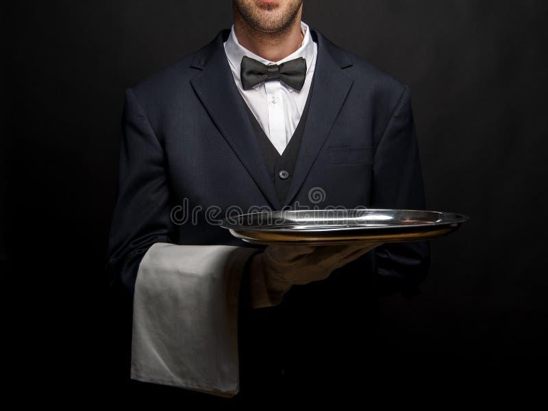 Kelner in het zwarte dienblad van de kostuumholding over zwarte achtergrond stock foto