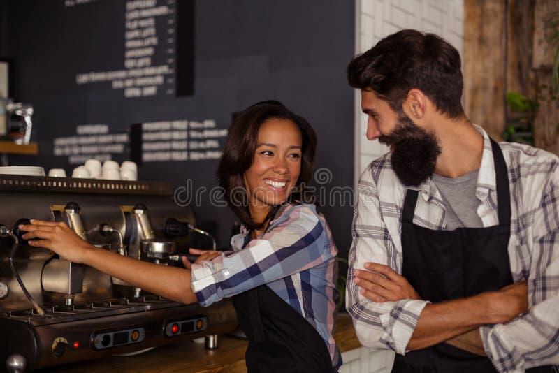 Kelner i kelnerka oddziała wzajemnie podczas gdy pracujący w kuchni obrazy royalty free