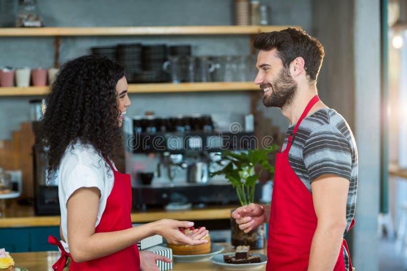 Kelner i kelnerka oddziała wzajemnie z each inny w café obraz stock