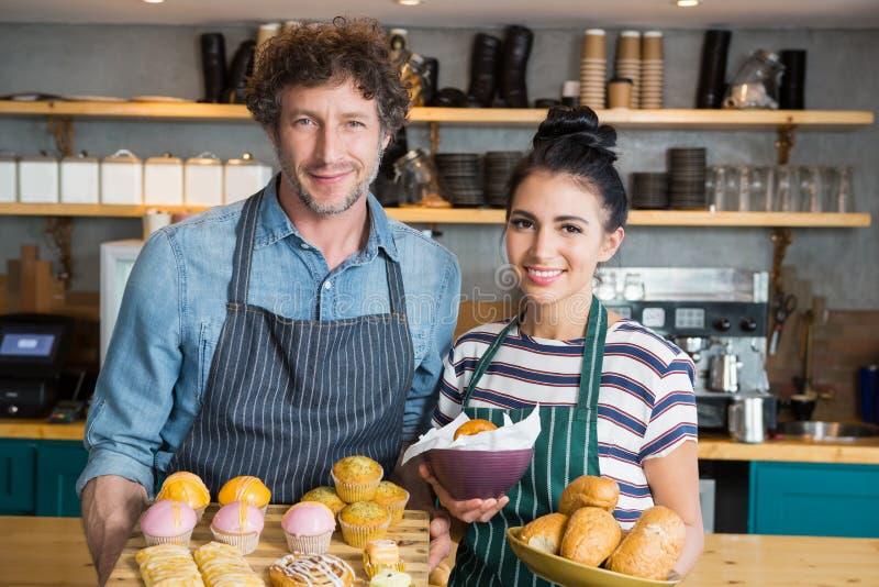 Kelner i kelnerka trzyma drewnianą tacę i puchar z przekąskami i deserem obrazy royalty free