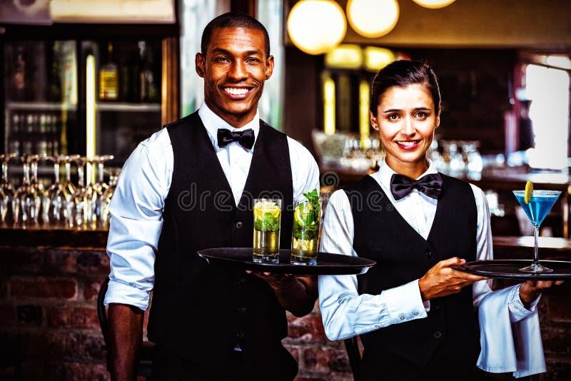 Kelner i kelnerka trzyma porci tacę z szkłem koktajl zdjęcie stock