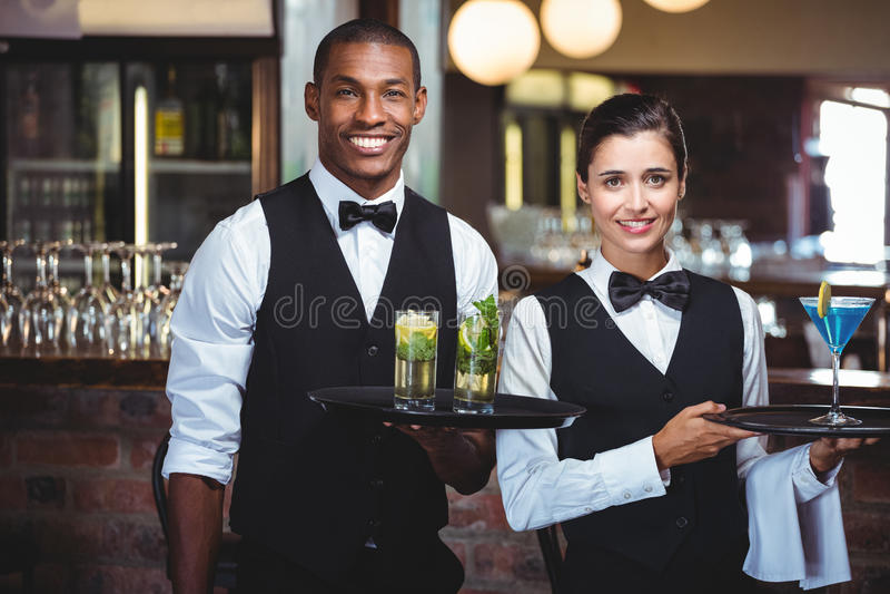 Kelner i kelnerka trzyma porci tacę z szkłem koktajl fotografia royalty free