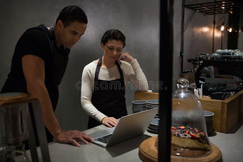 Kelner i kelnerki używa laptop przy kontuarem obraz stock