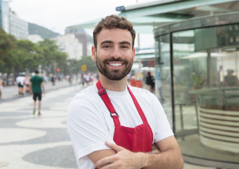 Kelner met baard en gekruiste wapens voor een restaurant stock foto's