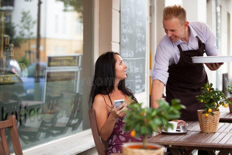 Kelner met een dienblad in een koffiewinkel stock afbeelding