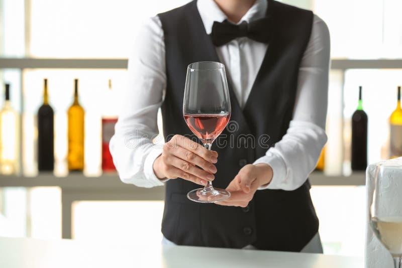 Kelner met glas wijn in bar stock foto's