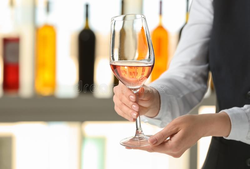 Kelner met glas wijn in bar stock afbeelding