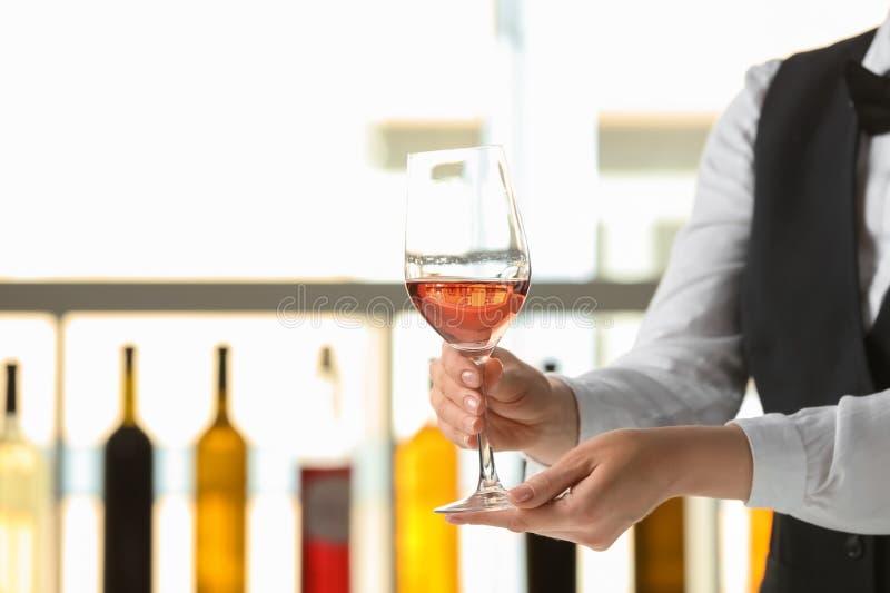 Kelner met glas wijn in bar royalty-vrije stock afbeeldingen