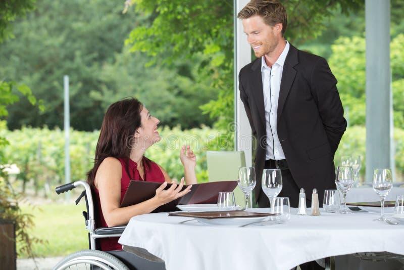 Kelner miewa skłonność niepełnosprawny gość restauracji zdjęcie royalty free