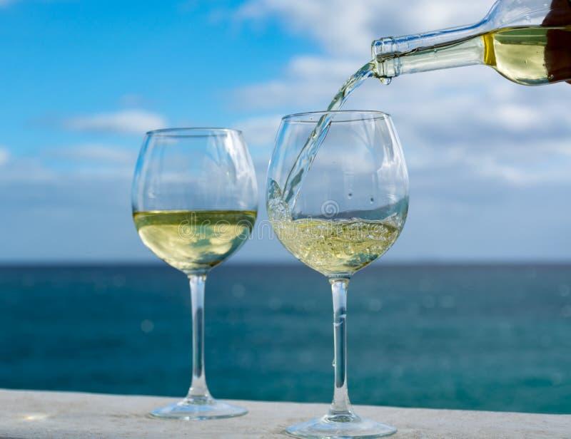 Kelner nalewa szkło biały wino na plenerowym tarasie z morzem v obraz royalty free