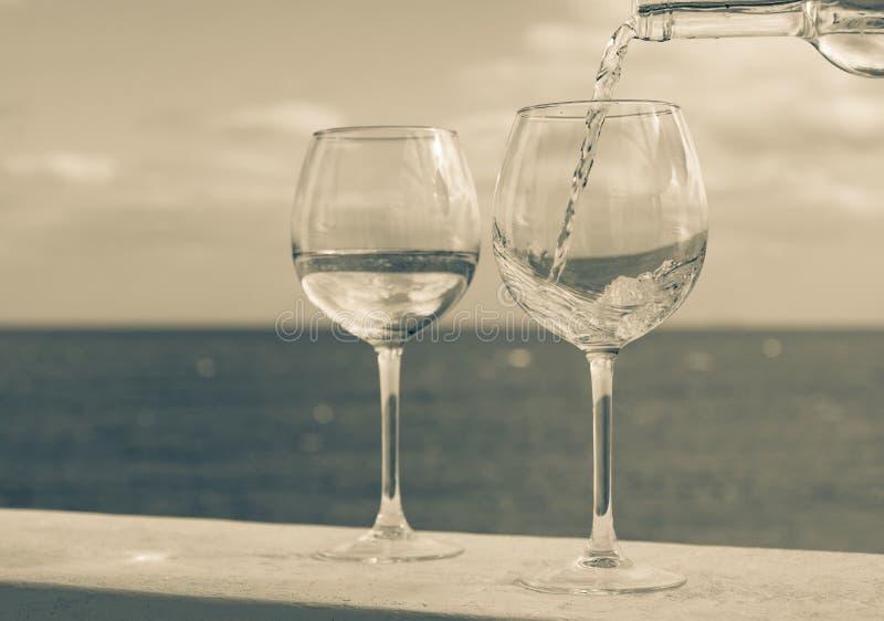 Kelner nalewa szkło biały wino na plenerowym tarasie z morzem v obrazy royalty free