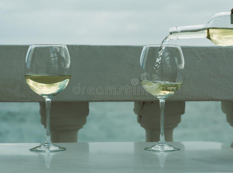 Kelner nalewa szkło biały wino na plenerowym tarasie z morzem v zdjęcia royalty free