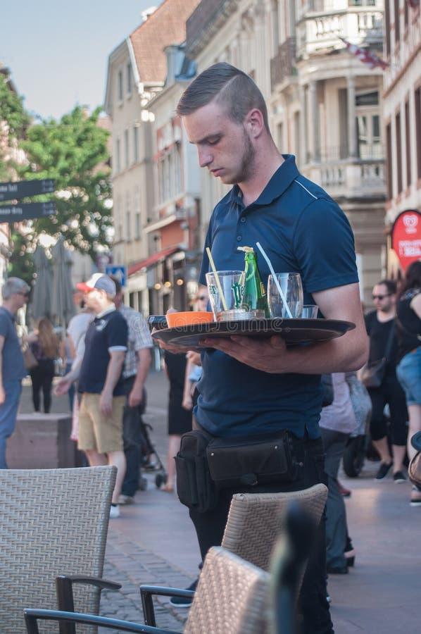 Kelner op het terras van de koffie Guillaume Tell in Mulhouse royalty-vrije stock afbeelding