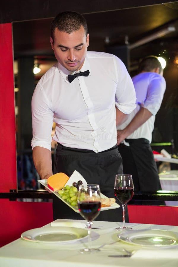 Kelner porci czerwone wino na stole i owoc zdjęcie stock
