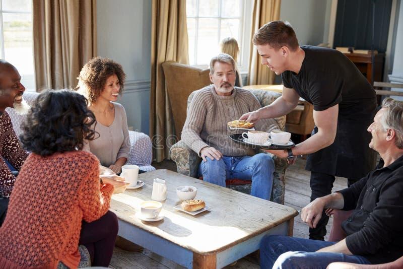 Kelner porci grupa Dojrzali przyjaciele W sklep z kawą obraz royalty free