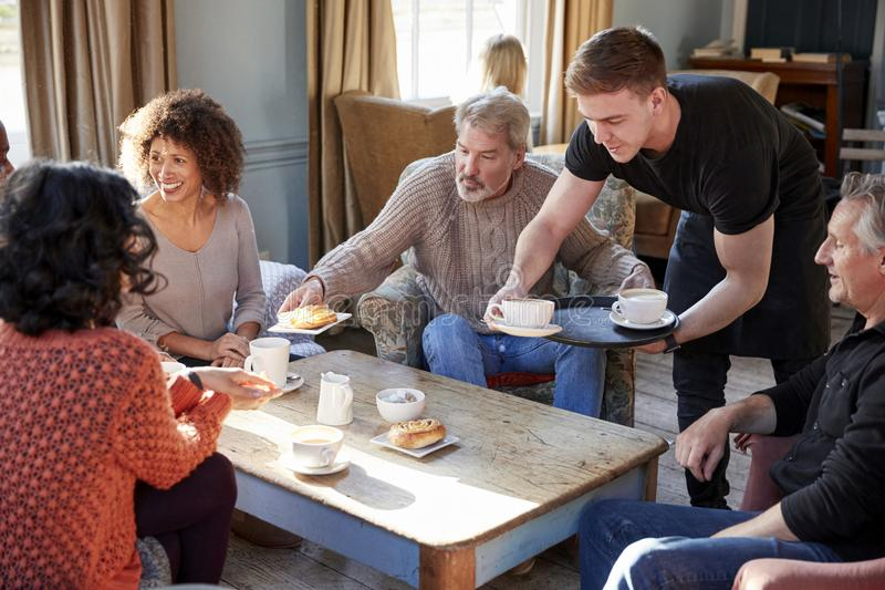 Kelner porci grupa Dojrzali przyjaciele W sklep z kawą obrazy royalty free
