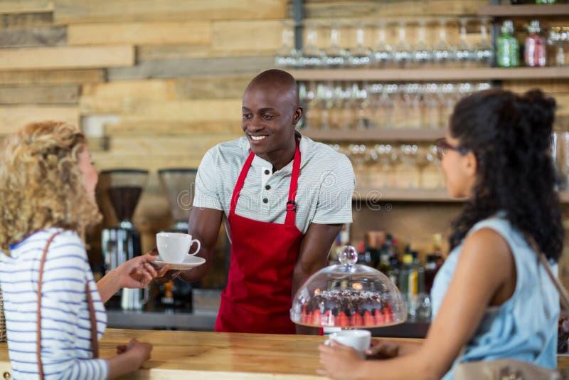 Kelner porci kawa żeński klient fotografia stock