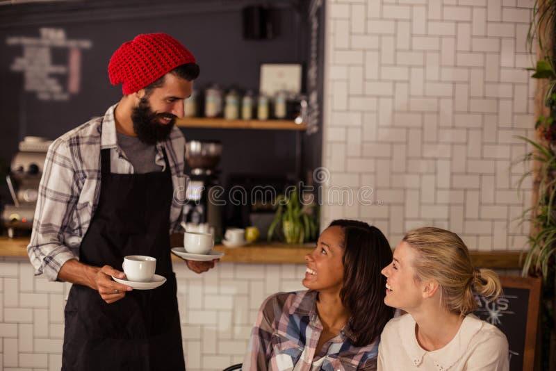 Kelner porci kawa i oddziałać wzajemnie z klientami zdjęcie royalty free
