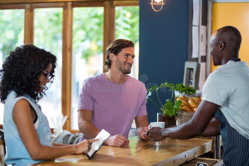 Kelner porci kawa obsługiwać podczas gdy kobieta używa cyfrową pastylkę przy kontuarem zdjęcia stock