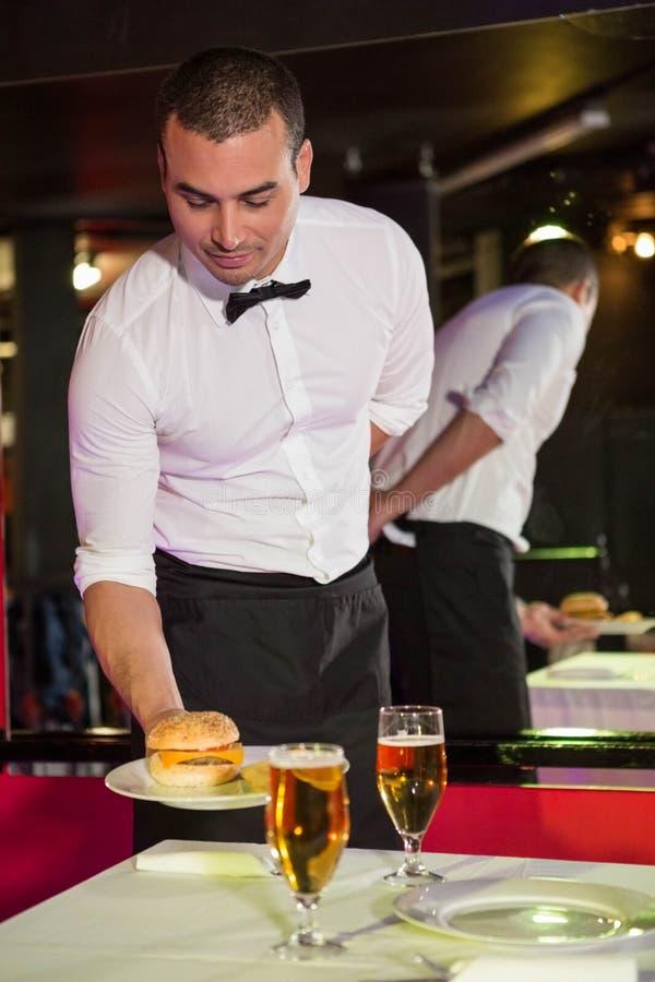 Kelner porci piwo na stole i hamburger zdjęcia royalty free
