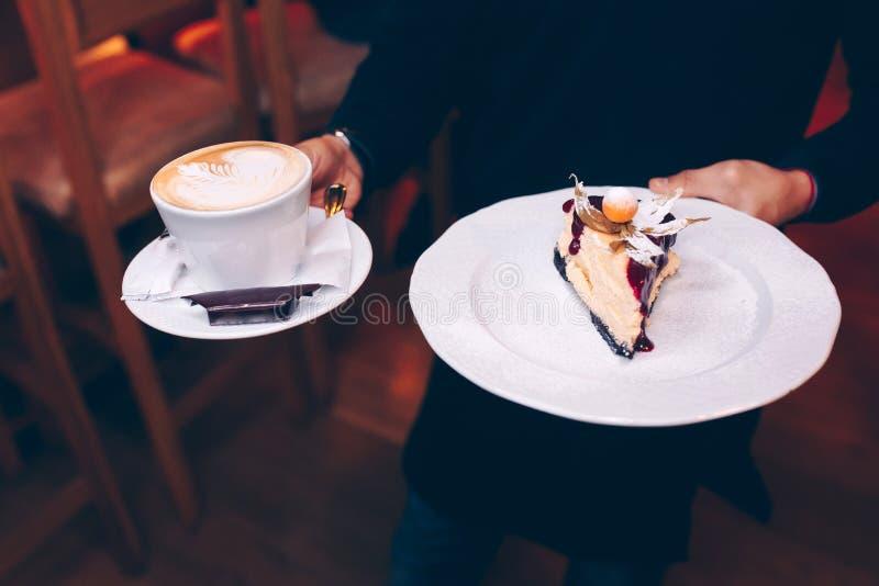Kelner porcji taca z wyśmienicie smakowitym Kawowym expresso, zakończenie w górę widoku deserowy kuchni tarta trzyma Naleśnikowy  obrazy royalty free