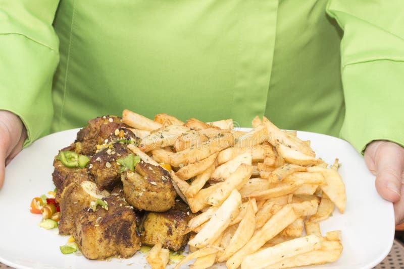 Kelner przynosi talerza pieczonej wołowiny i grul dłoniaki obrazy royalty free
