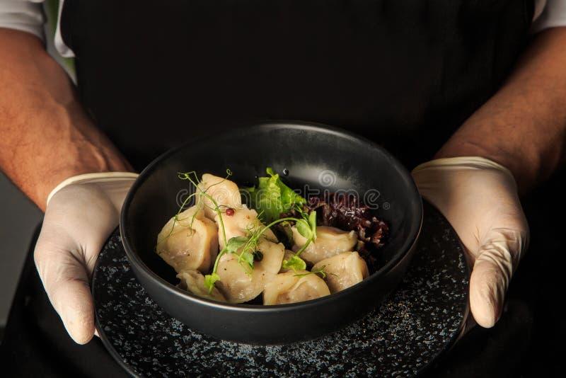 kelner ręk chwyt gotował się mięsne kluchy z sałatką w pucharze zdjęcia royalty free