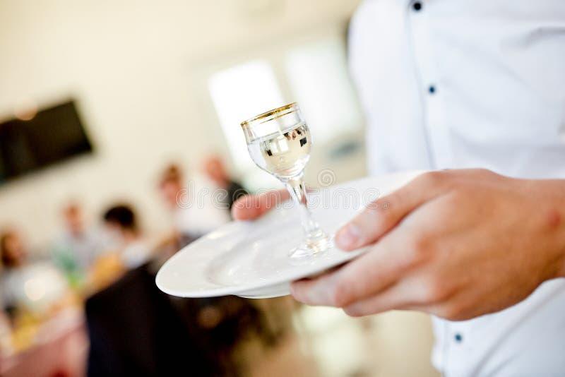 Kelner ręki trzymają talerza na którym jest szkło ajerówka fotografia stock