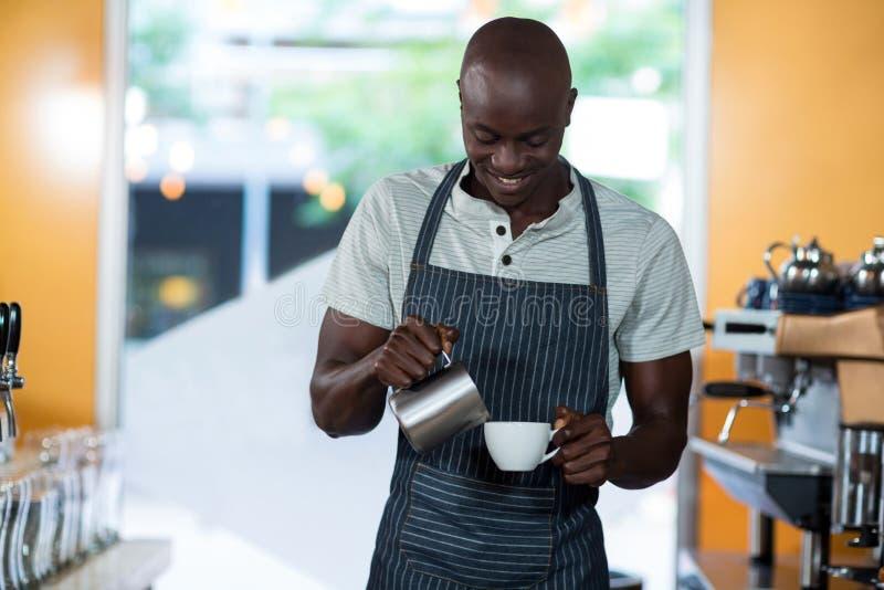 Kelner robi filiżance kawy przy kontuarem zdjęcie royalty free