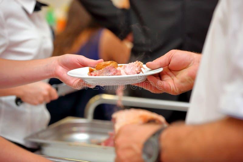 Kelner słuzyć piec mięsne i piec grule przy przyjęciem zdjęcie stock