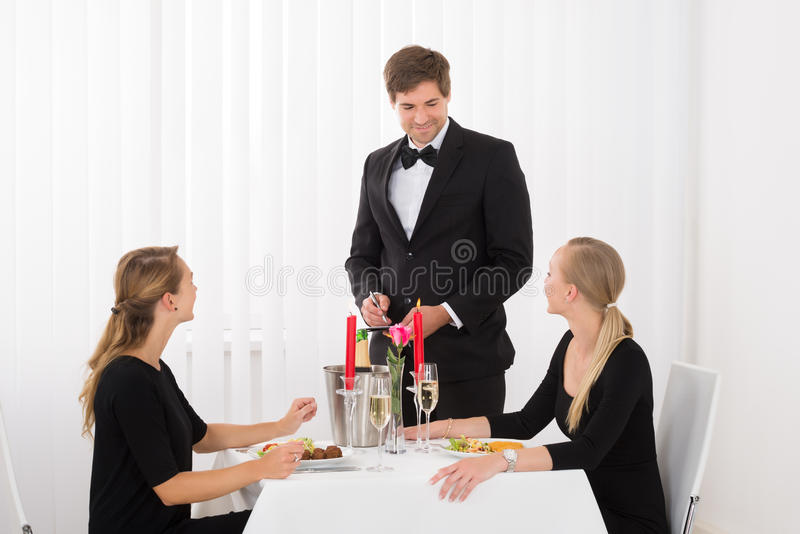 Kelner Taking An Order van Vrouwelijke Vrienden stock afbeelding