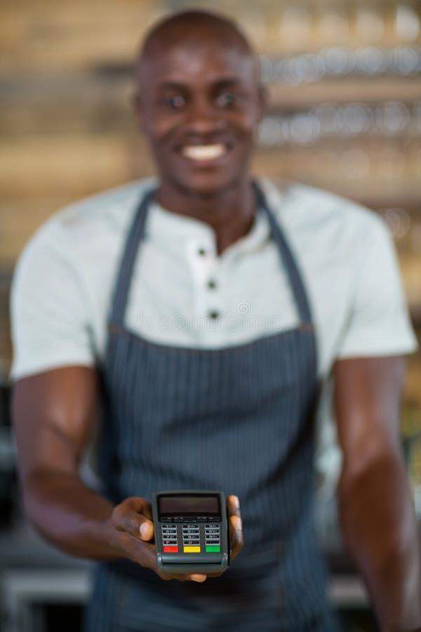 Kelner trzyma kredytowego czytnika kart zdjęcie royalty free
