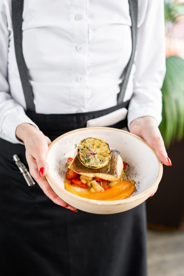 Kelner trzyma talerz orzechowy lub dorsz z pieczonymi warzywami Dysza ozdobiona kawałkiem cytryny zdjęcie stock